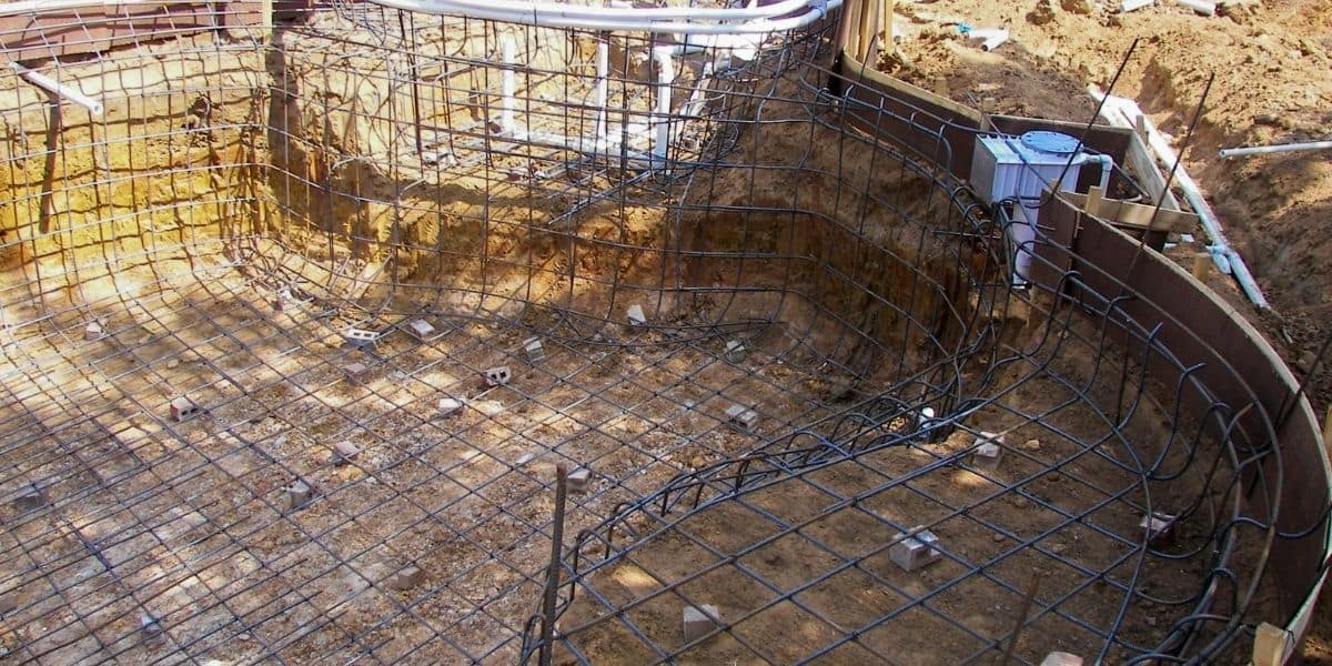 A new pool construction site with exposed earth and rebar.