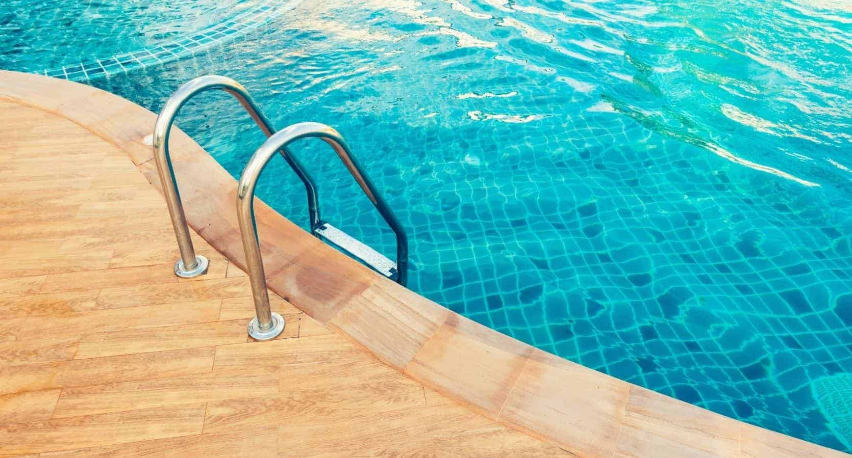 a decorative image of the side of a pool with a ladder going into the water.
